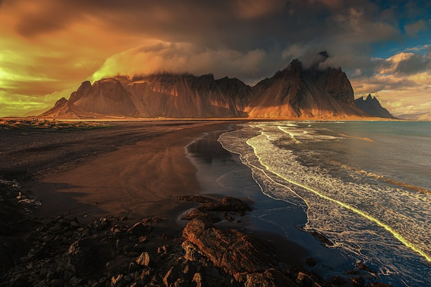 Aerial beautiful shot of a seashore with hills on the background at sunset Free Photo