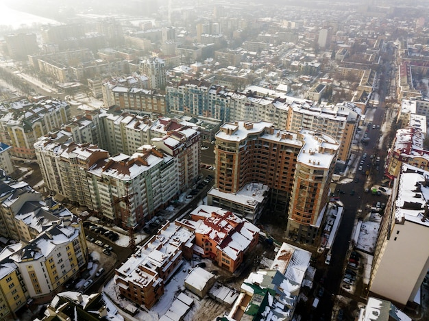 Aerial black and white winter top view of modern city center with tall buildings and parked cars on snowy streets. Premium Photo