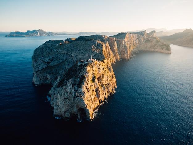Ripresa aerea distante di un'alta scogliera rocciosa con una torre bianca costruita in cima all'oceano Foto Gratuite