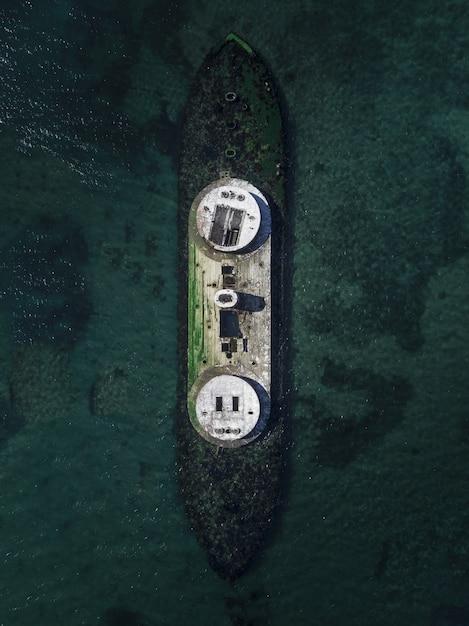 Colpo aereo del fuco di una nave demolita nel mare Foto Gratuite