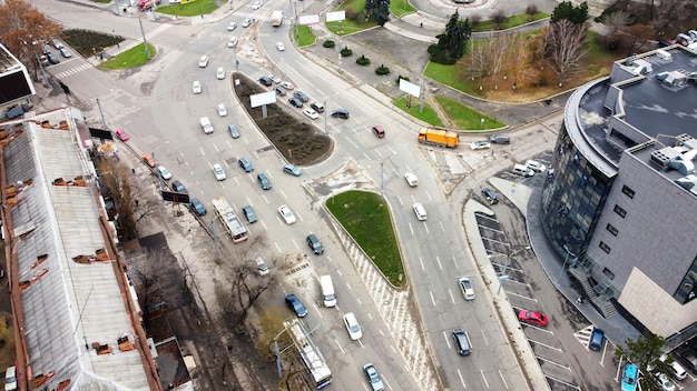 Aerial drone view of chisinau, road with multiple moving cars, roundabout intersection, bare trees, top view Free Photo
