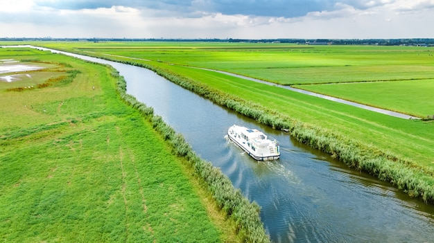 Aerial drone view of houseboat in canal and country landscape of holland from above, family travel by barge boat and vacation in netherlands Premium Photo