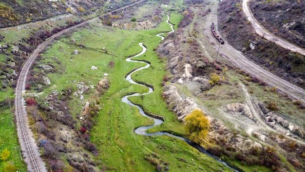 몰도바 자연의 공중 무인 항공기보기, 계곡으로 흐르는 개울, 드문 드문 식물과 바위가있는 슬로프, 움직이는 기차, 흐린 하늘 무료 사진