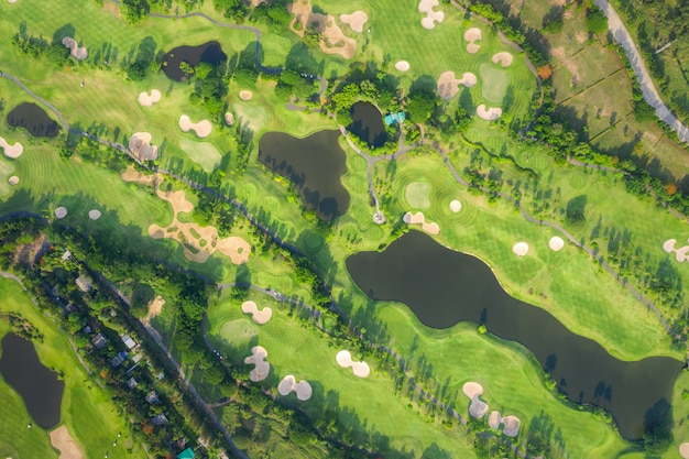Aerial panoramic view drone shot of beautiful golf course with people playing golf in field. Premium Photo