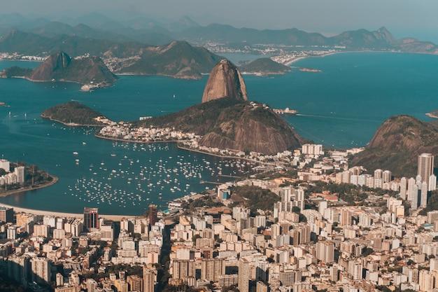 Foto aerea di rio de janeiro circondato dal mare e dalle colline sotto la luce del sole in brasile Foto Gratuite
