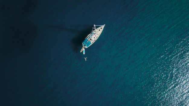 Aerial shot of beautiful blue lagoon at hot summer day with sailing boat. top view. Premium Photo