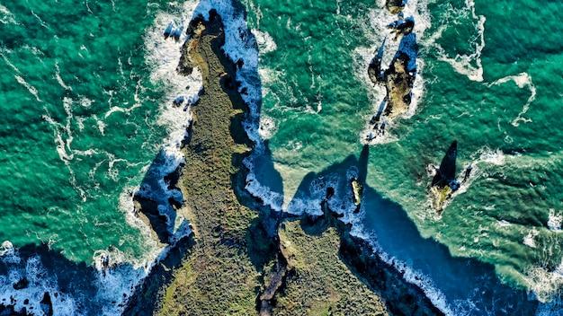 Ripresa aerea di bellissime barriere coralline e sorprendente trama dell'acqua nell'oceano Foto Gratuite
