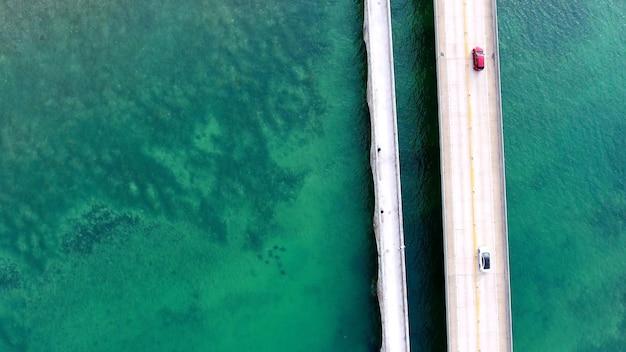 Ripresa aerea di auto che guidano su un ponte sul mare in florida Foto Gratuite