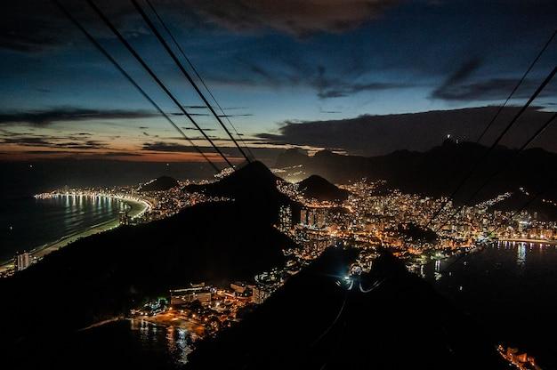 Ripresa aerea di luci di edifici della città di notte vicino al mare e alle montagne Foto Gratuite
