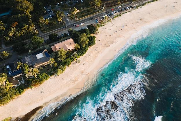 Ripresa aerea di case e strade vicino alla spiaggia sabbiosa Foto Gratuite