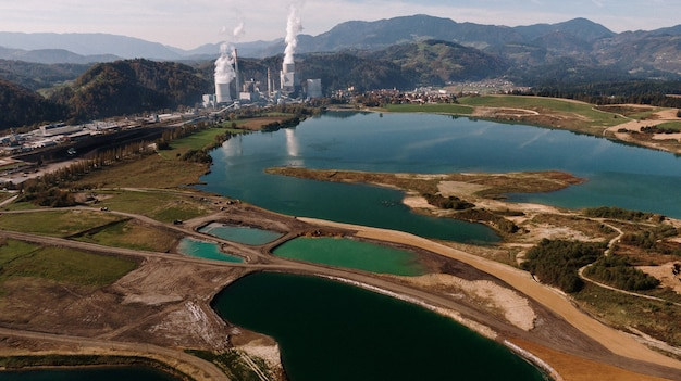Aerial shot of a landscape surrounded by mountains and lakes with industrial disaster Free Photo