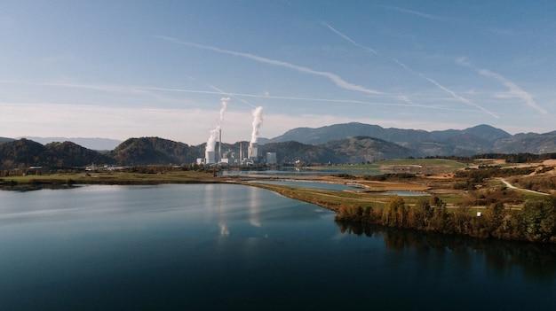 Ripresa aerea di un paesaggio circondato da montagne e laghi con disastro industriale Foto Gratuite