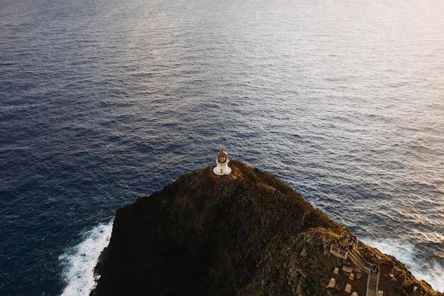 Ripresa aerea di un faro in cima alla scogliera in mare aperto Foto Gratuite