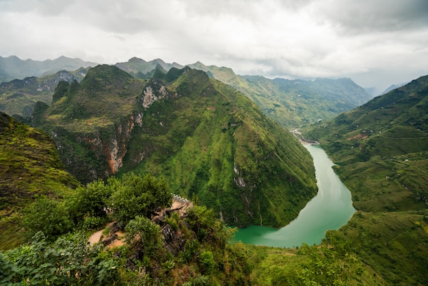 Aerial shot of a narrow river in the mountains under the cloudy sky in vietnam Free Photo