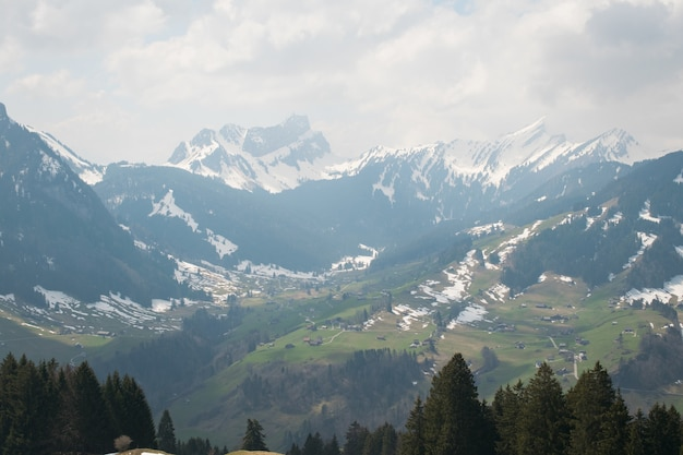 曇り空の下で雪で覆われた美しい山脈の空中ショット 無料写真
