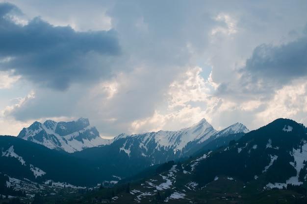 曇り空の下で雪に覆われた美しい山脈の空中ショット 無料写真