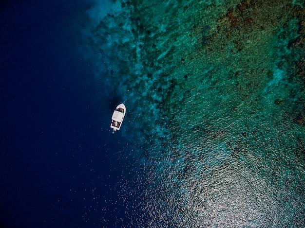 ボネール島、カリブ海の美しい青い海でボートの空中ショット 無料写真