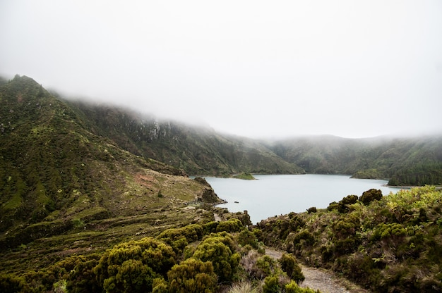 緑の丘と霧の中で森林に覆われた山に囲まれた池の空中ショット 無料写真