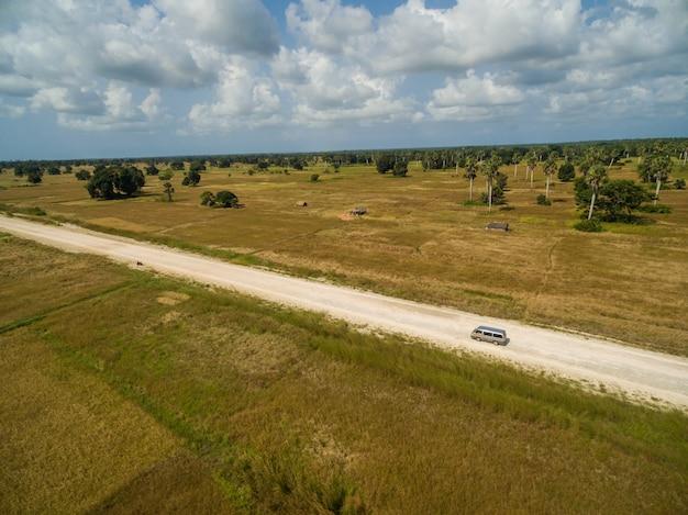 Воздушная съемка дороги, окруженной травой покрыты поля, захваченные в занзибаре, африка Бесплатные Фотографии