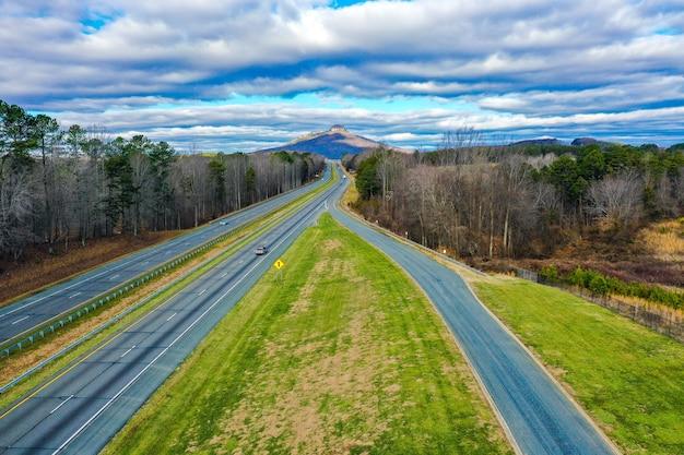 노스 캐롤라이나, 미국에서 파일럿 산과 흐린 푸른 하늘 도로의 공중 샷 무료 사진