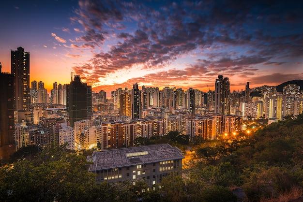 日没時のオレンジ色の空の下で街のスカイラインの空中ショット 無料写真