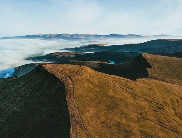 白い雲に囲まれた山々の空中ショット 無料写真