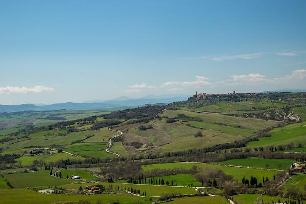 Снимок захватывающих дух полей, покрытых травой, под красивым небом, сделанный в италии. Бесплатные Фотографии