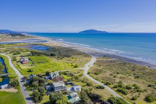 Ripresa aerea della spiaggia di otaki in nuova zelanda che mostra l'isola di kapiti in lontananza Foto Gratuite