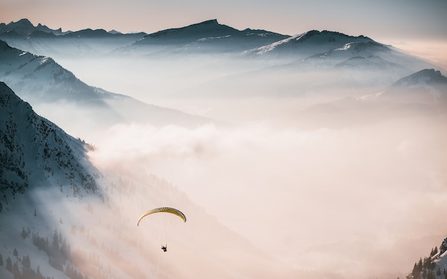 Aerial shot of a person parachuting down above the clouds near snowy mountains Free Photo
