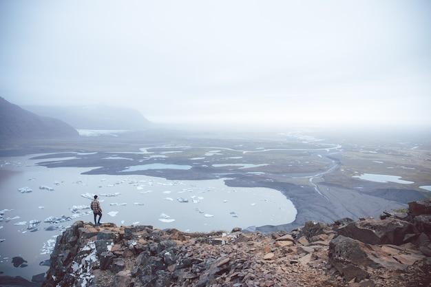 Ripresa aerea di una persona in piedi su una scogliera che domina i laghi nella nebbia catturata in islanda Foto Gratuite