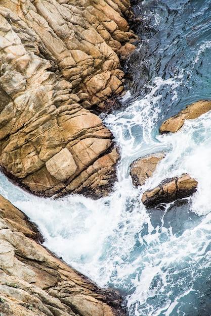 Ripresa aerea delle onde del mare che colpiscono le rocce Foto Gratuite