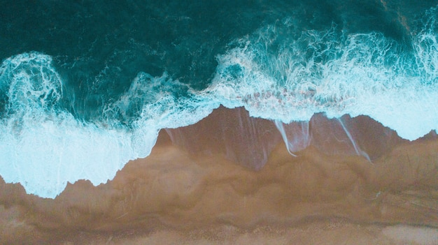 Aerial shot of sea waves hitting the sandy shore Free Photo