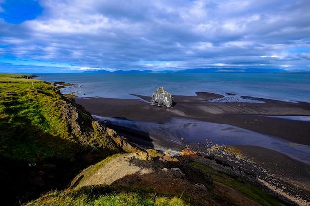 Ripresa aerea del litorale vicino a una collina erbosa sotto un cielo nuvoloso Foto Gratuite