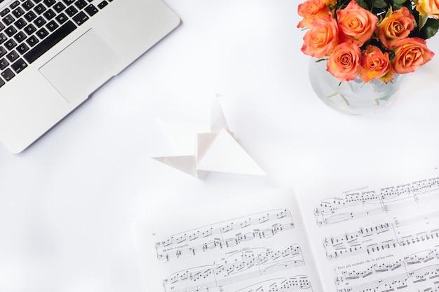Ripresa aerea di una scrivania bianca con un foglio di carta origami fiori di carta e un computer portatile Foto Gratuite