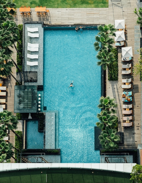 Aerial of swimming pool with floating bar, people lay down on the beach chairs and a man swimming in summer. Premium Photo