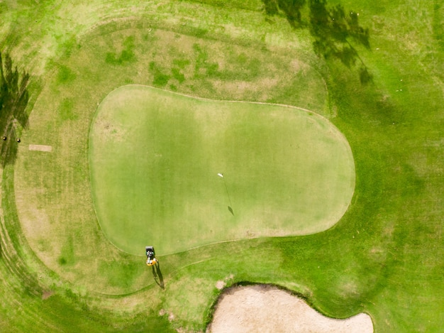 Aerial top view golf course, lush green grass on golf course with path for golf cart, man cutting the grass with electric lawn mower and flag Premium Photo