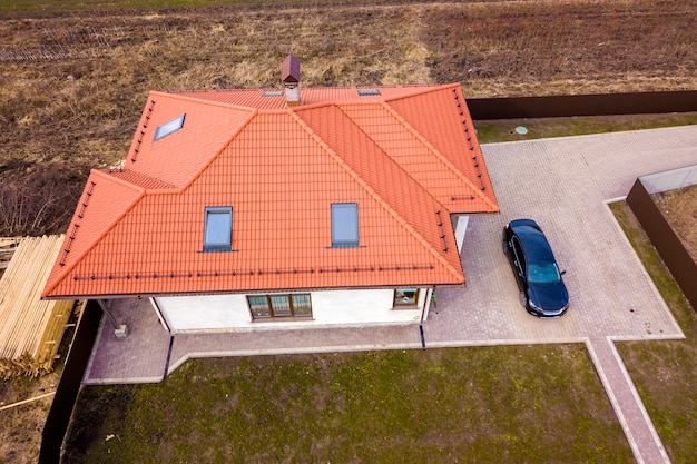 Aerial top view of house metal shingle roof with attic windows and black car on paved yard. Premium Photo