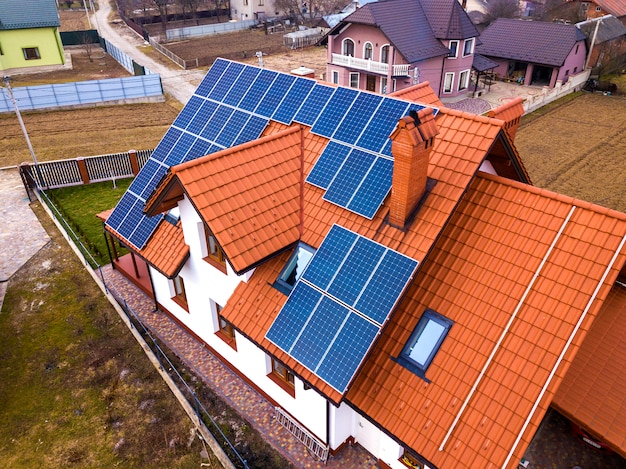 Aerial top view of new modern residential house cottage with blue shiny solar photo voltaic panels system on roof. renewable ecological green energy production concept. Premium Photo