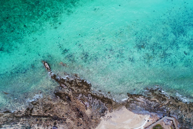 Aerial top view of ocean waves, beach and rocky coastline and beautiful forest. Premium Photo