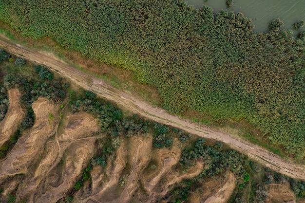 Вид сверху с воздуха на сельскую дорогу, разделяющую мельницу и песчаные дюны. Бесплатные Фотографии