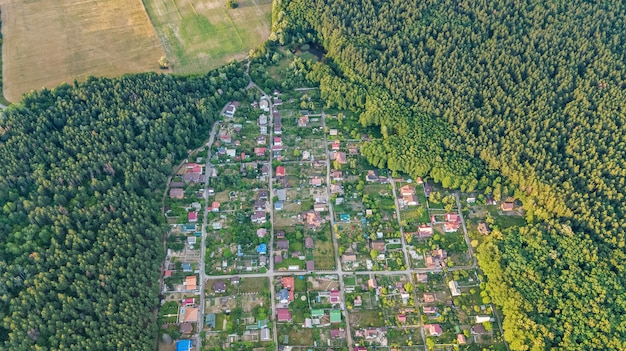 Aerial top view of residential area summer houses in forest from above, countryside real estate and small dacha village in ukraine Premium Photo
