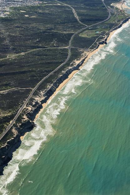 Воздушный вертикальный снимок дороги посреди травянистых полей у берега пляжа Бесплатные Фотографии