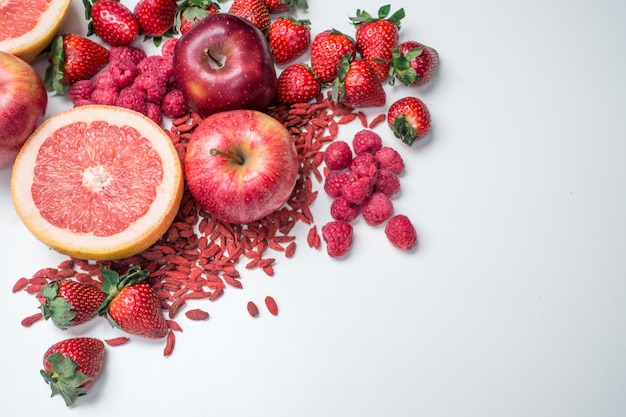 Aerial vibrant shot of red fruit and vegetables on a white background Free Photo