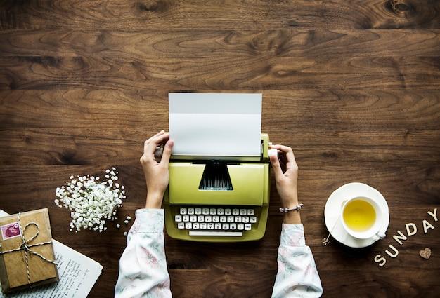 Аэрофотосъемка женщины с использованием ретро-пишущей машинки для хобби и концепции отдыха в воскресенье Бесплатные Фотографии