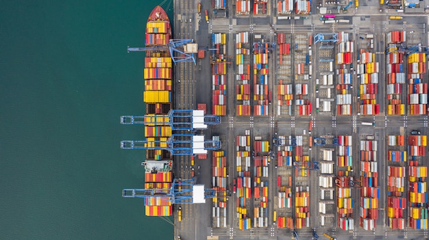 Aerial view cargo ship terminal, unloading crane of cargo ship terminal, aerial view industrial port with containers and container ship. Premium Photo