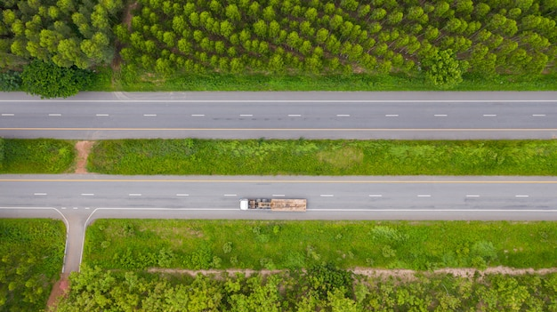 Aerial view of cars and trucks on asphalt road passes through the green forest Premium Photo
