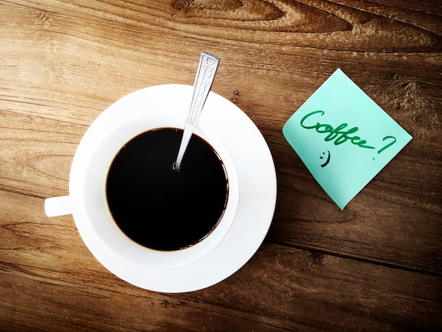 Aerial view of coffee cup on wooden table with sticky note Free Photo