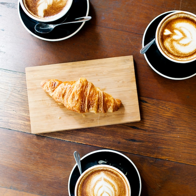 Aerial view of coffee cups and croissant on wooden table Free Photo