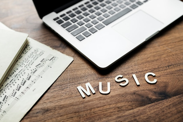 Aerial view of computer laptop on wooden table and letters forming the word music Free Photo