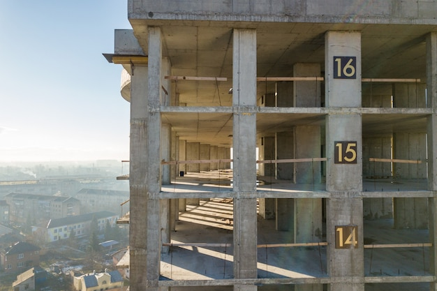 Aerial view of concrete frame of tall apartment building under construction in a city. Premium Photo